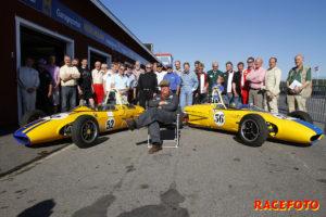 Picko Troberg poserar glatt framför två gamla Formula Juniorbilar som han själv har kört plus alla förarna som körde i klassen under tävlingen i fjol.